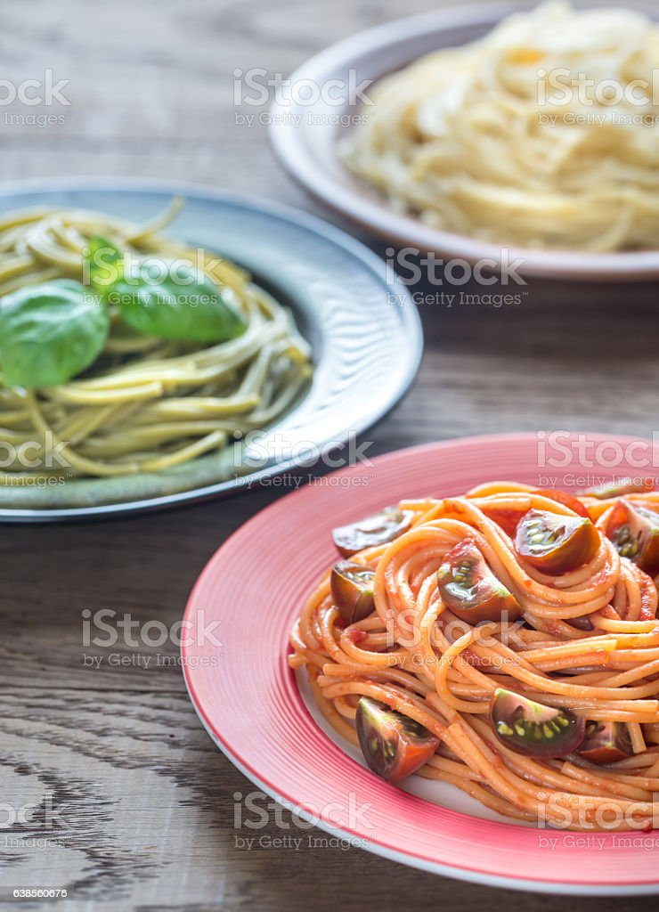 Portions of colorful spaghetti with ingredients stock photo