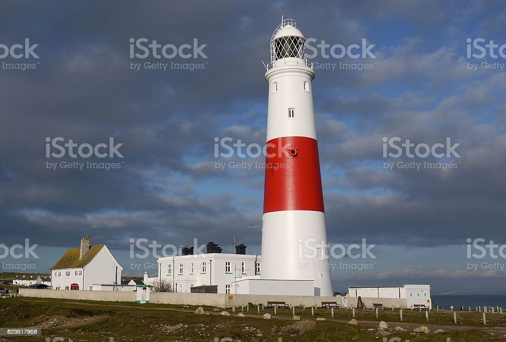 Portland Bill lighthouse and white buildings against dark skies. stock photo