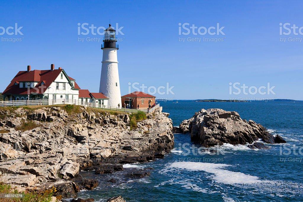 Portland Head Light, rocks, ocean surf, in morning. Blue sky. stock photo