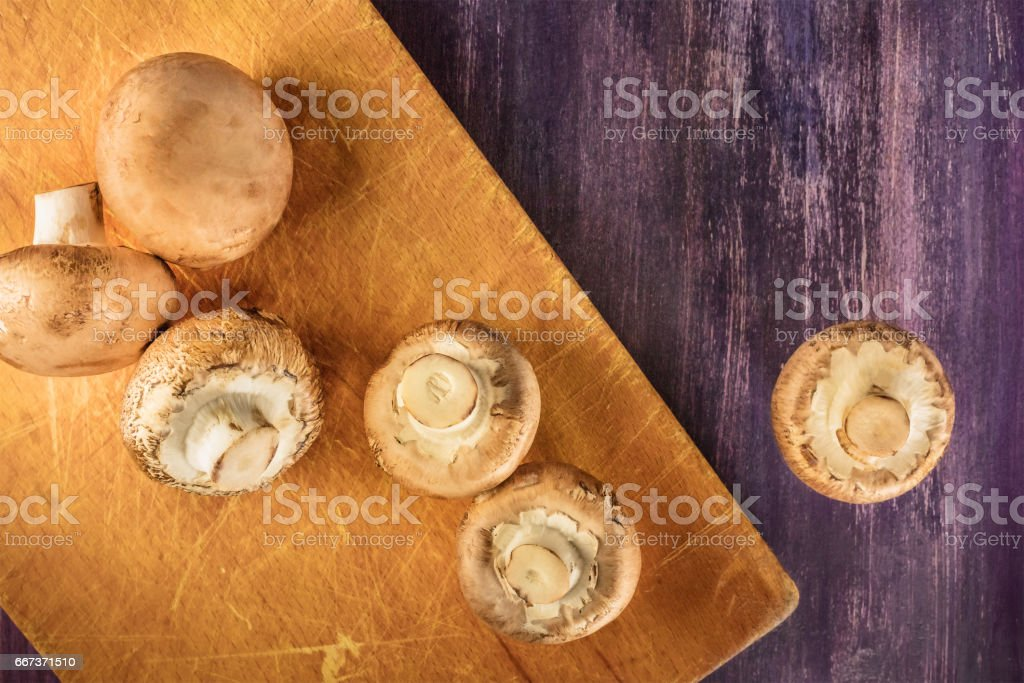 Portobello mushrooms on wooden cutting board with copyspace stock photo