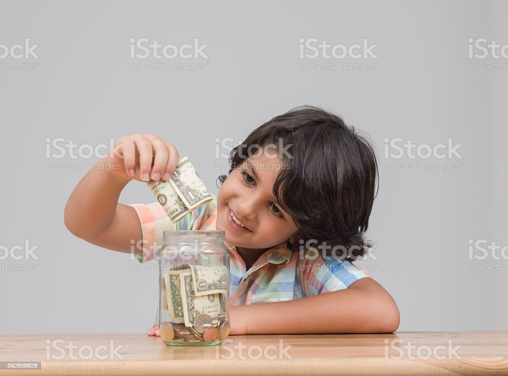 Portraiit of child putting money in savings jar stock photo