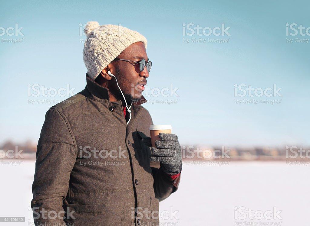 Portrait african man enjoying drinking coffee over sky in winter stock photo