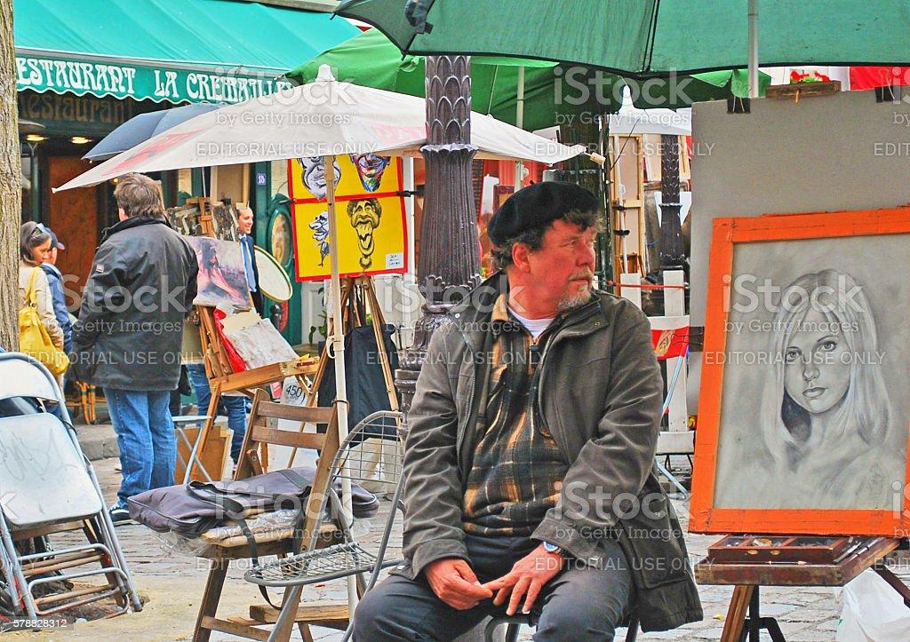 Portrait artist seated beside his work, Montmartre, Paris stock photo