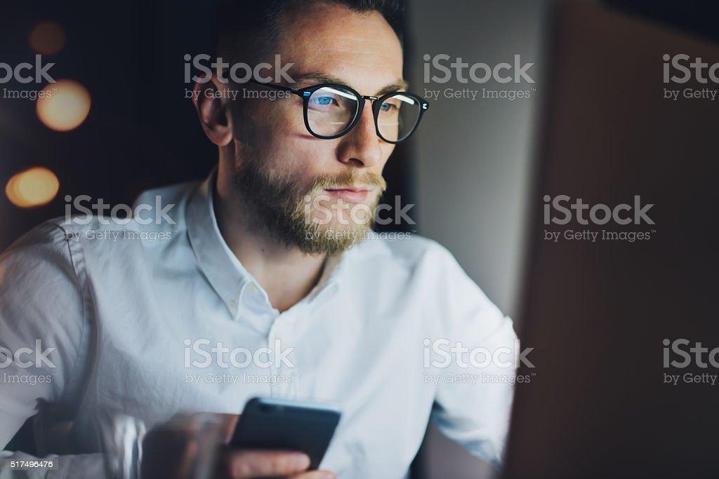 Portrait bearded businessman working on modern loft office at night stock photo