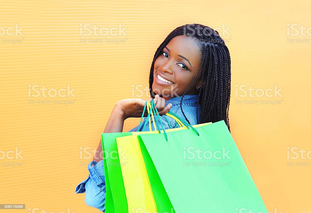 Portrait beautiful smiling african woman with shopping bags in city stock photo