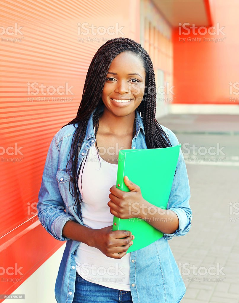 Portrait beautiful smiling young african woman with folder stock photo