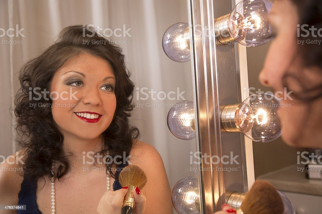 Portrait:  Beautiful young woman's reflection in a hollywood make-up mirror. royalty-free stock photo