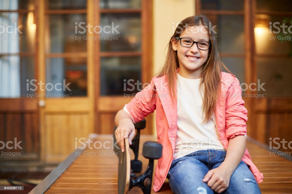 Portrait before going to school with skateboard. stock photo