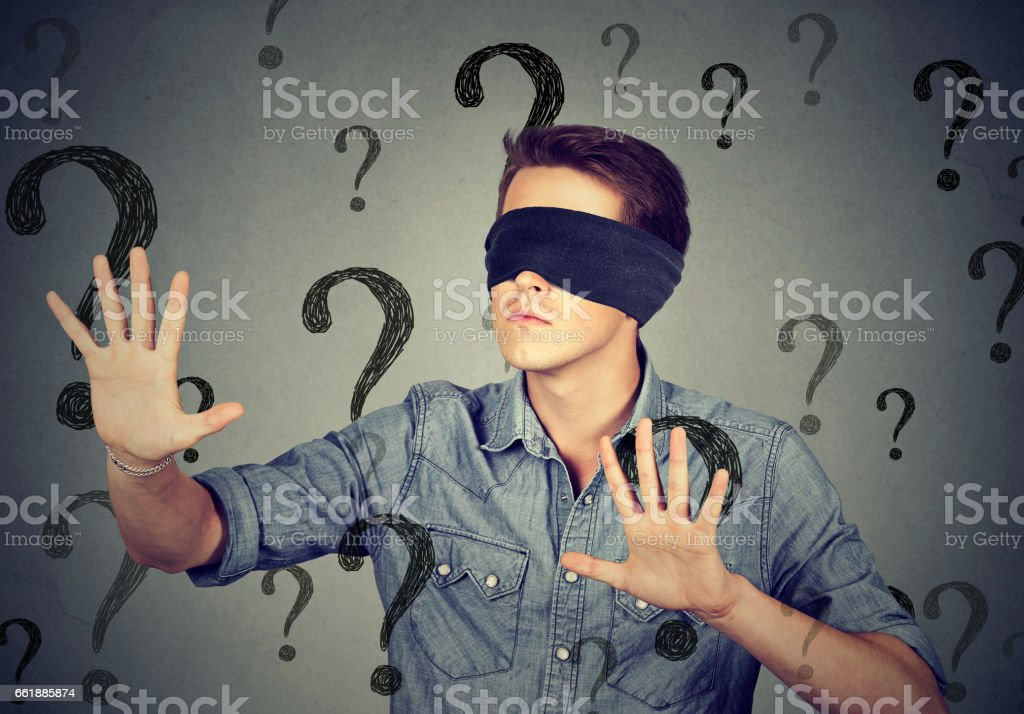 Portrait blindfolded man stretching his arms out walking through many question marks stock photo