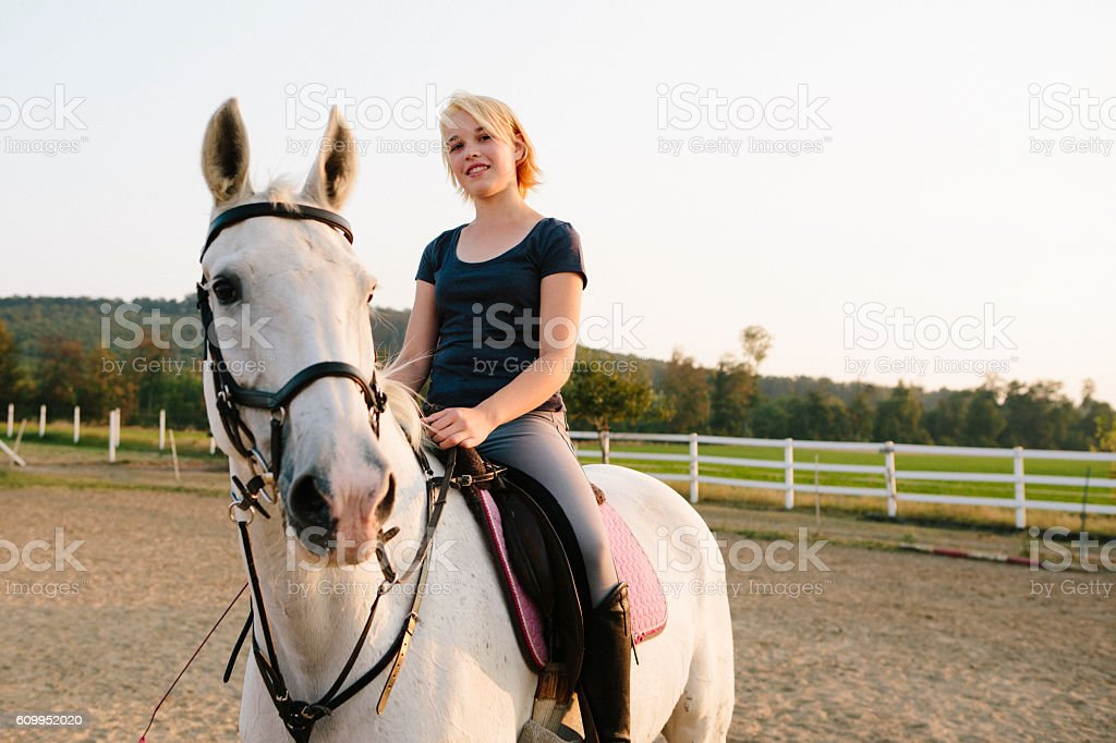 Portrait: blonde teenager girl rides her white horse outdoors stock photo