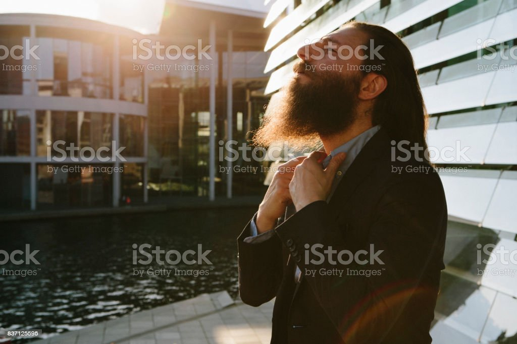 Portrait: businessman with long hair and beard, back lit, rebellion stock photo