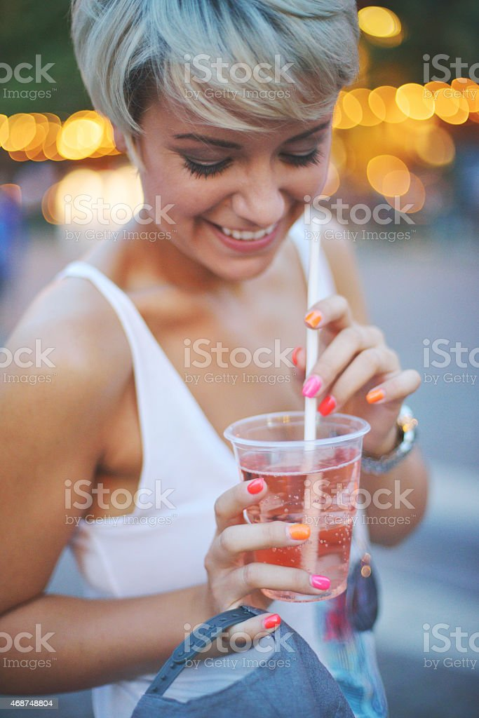 Portrait from a young beautiful woman drinking on a festival stock photo