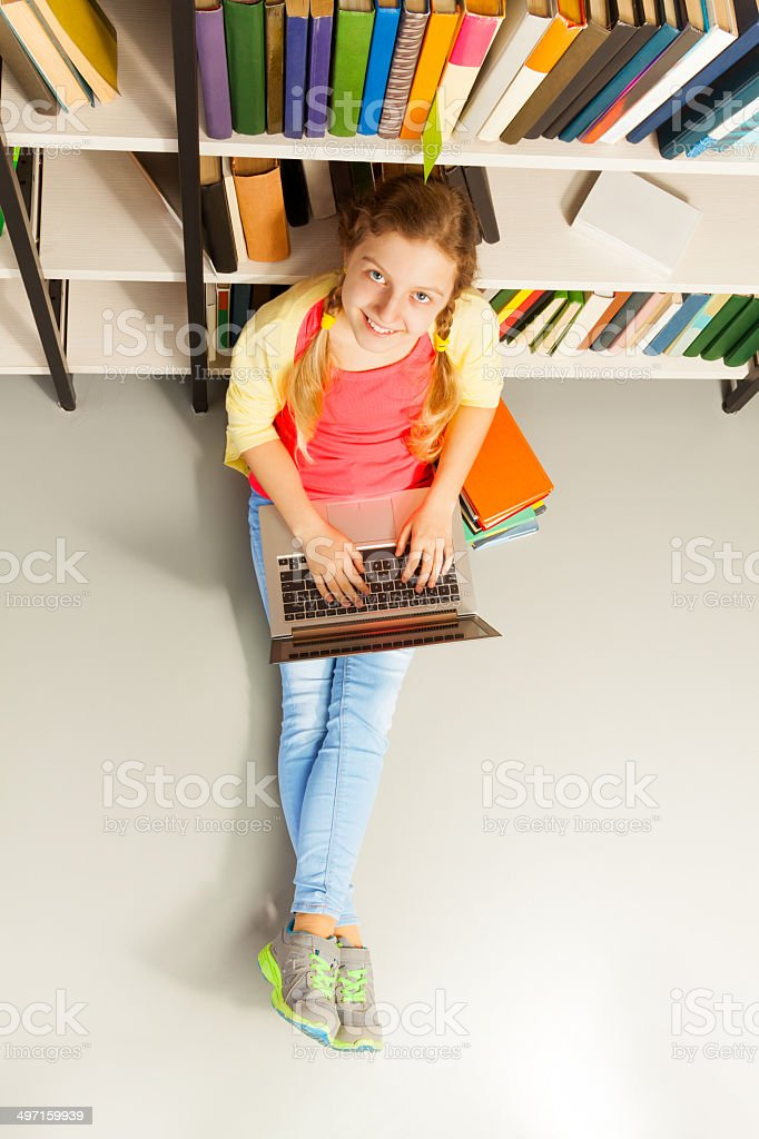 Portrait from above of smiling girl with laptop stock photo