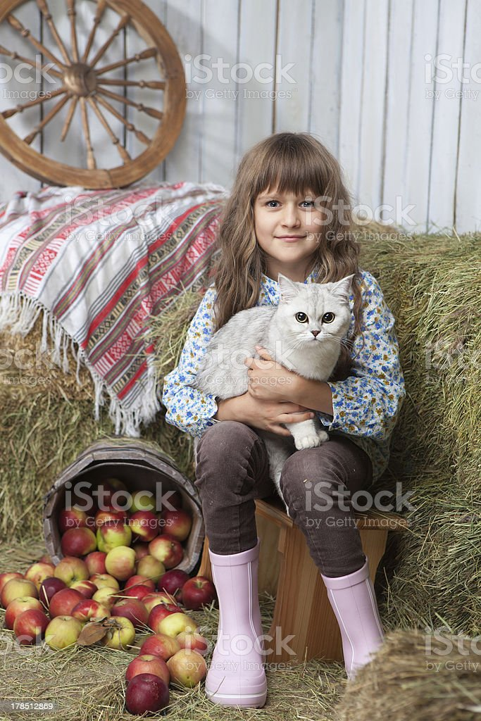 Portrait girl villager with cat near pail, apples in hayloft royalty-free stock photo