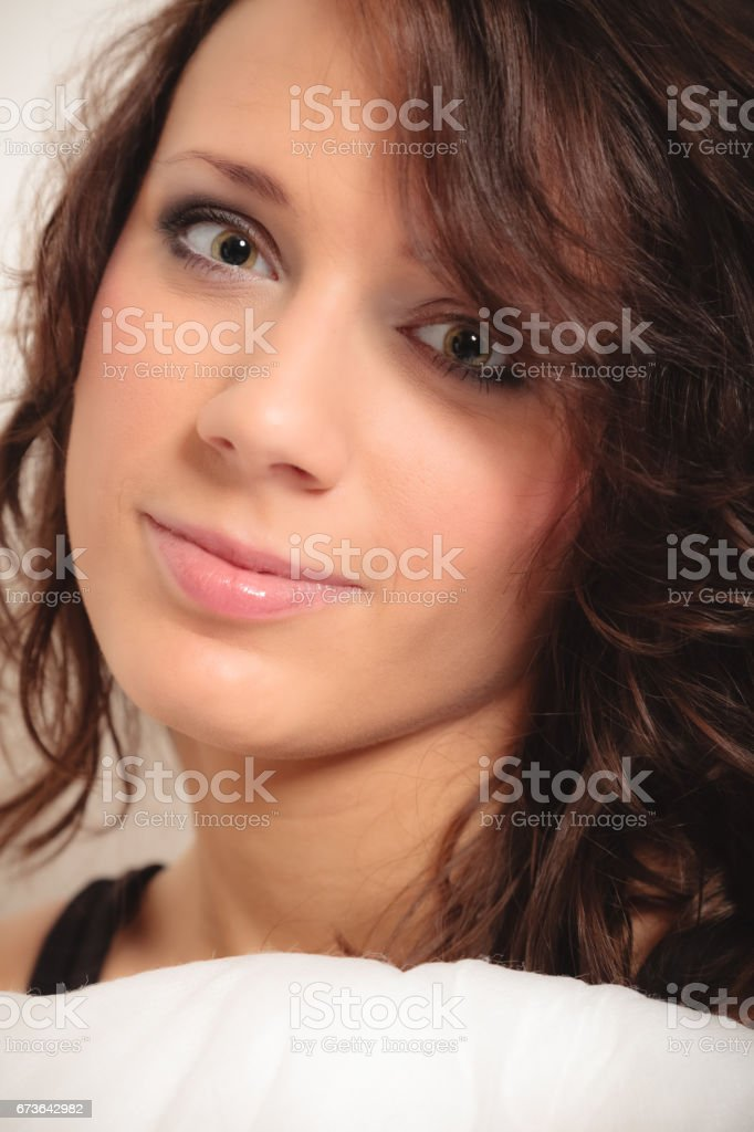 Portrait girl with pillow. Woman with curly hair stock photo