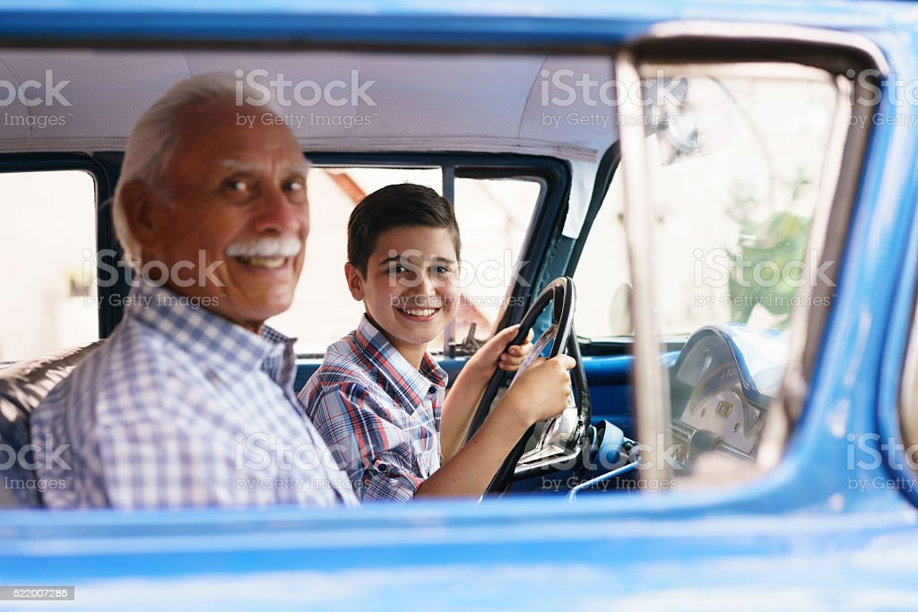 Portrait Grandpa Giving Driving Lesson To Boy In Old Car stock photo
