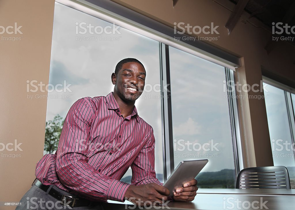portrait happy african american male with digital  tablet by window royalty-free stock photo