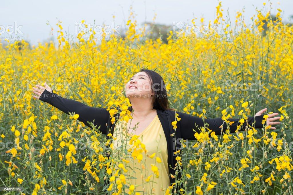 Portrait happy fat woman in yellow flower garden stock photo