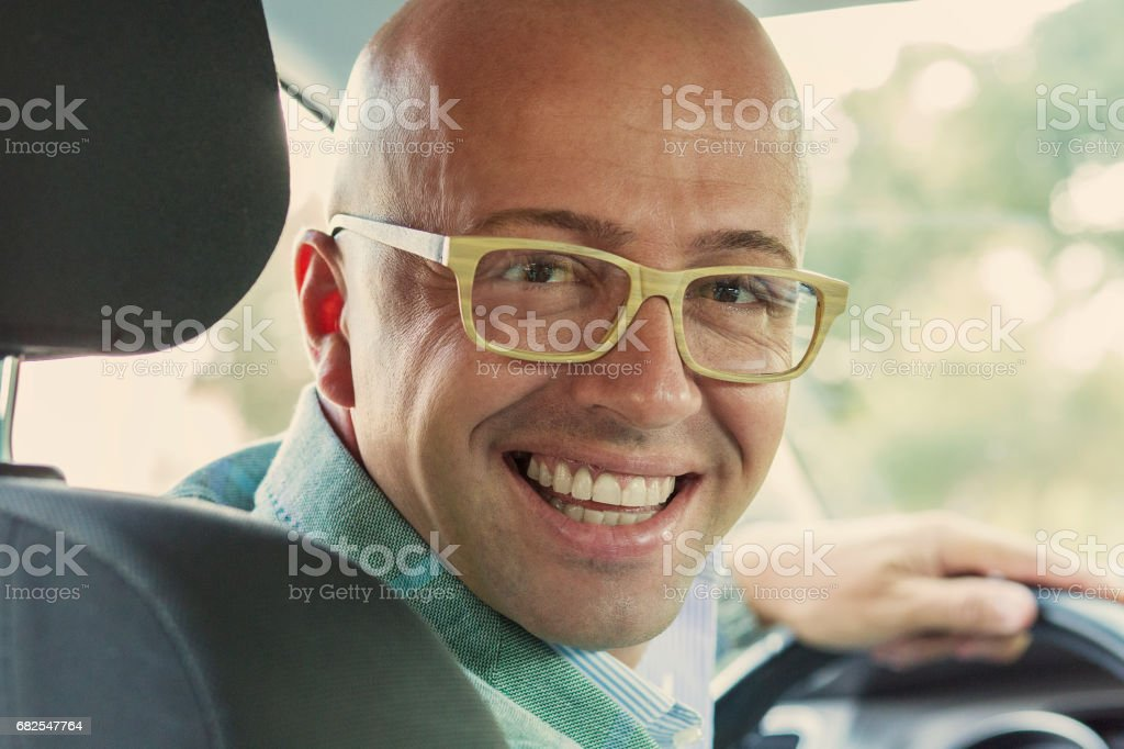Portrait happy handsome young man in new car hands on wheel, turning around, smiling looking at, talking to passengers sitting in back seat. Driver license test concept stock photo