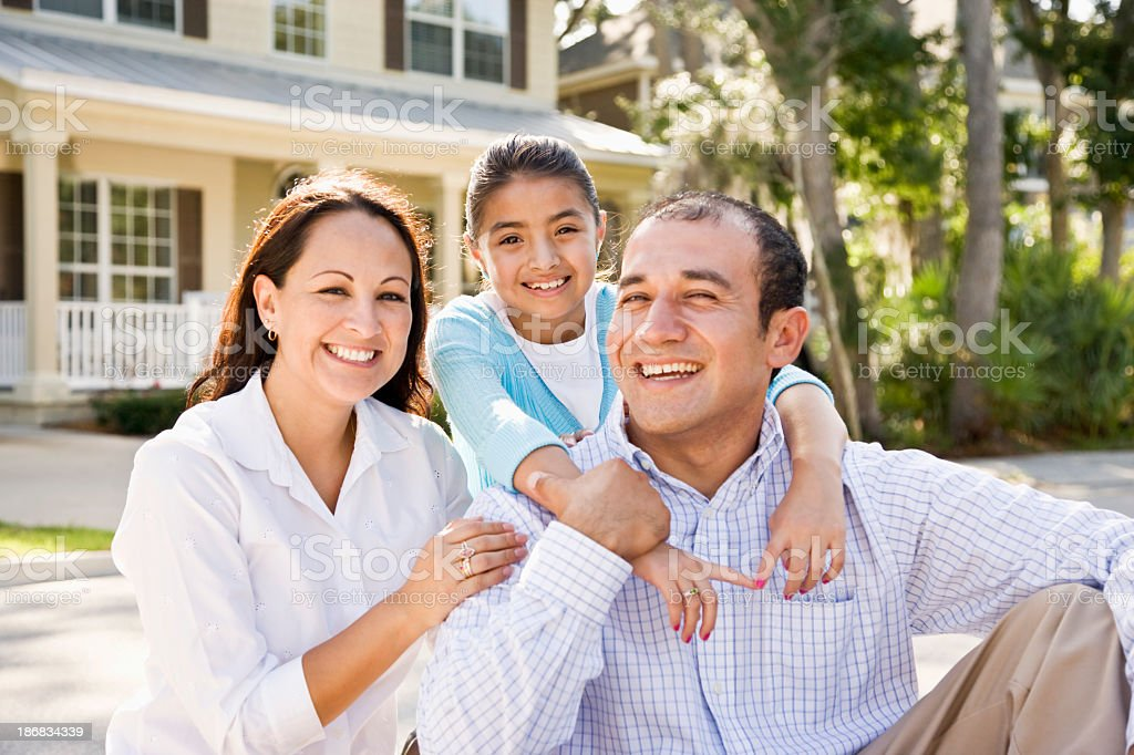 Portrait happy Hispanic family sitting with house in background royalty-free stock photo