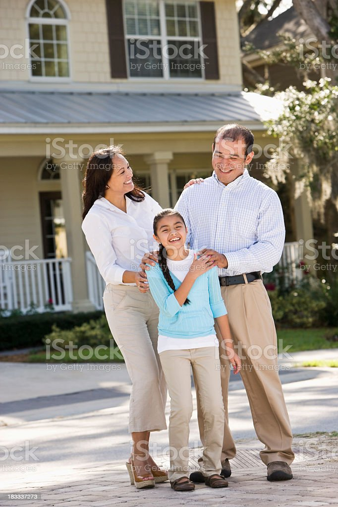 Portrait happy Hispanic family standing in front of house stock photo
