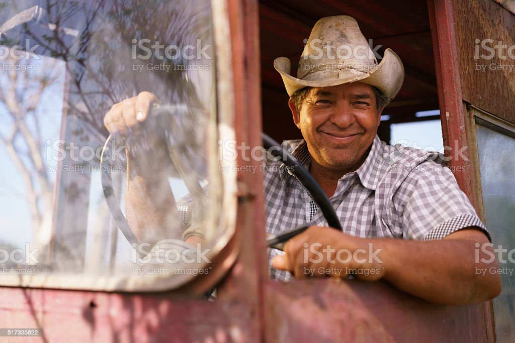 Portrait Happy Man Farmer Driving Tractor Looking At Camera stock photo