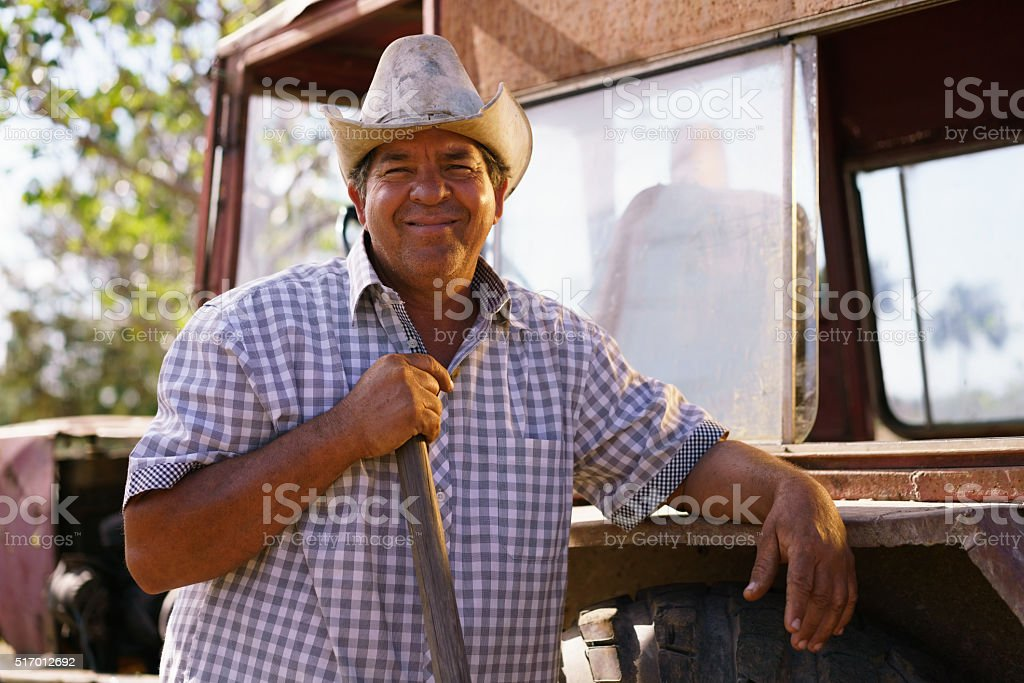 Portrait Happy Man Farmer Leaning On Tractor Looking At Camera stock photo