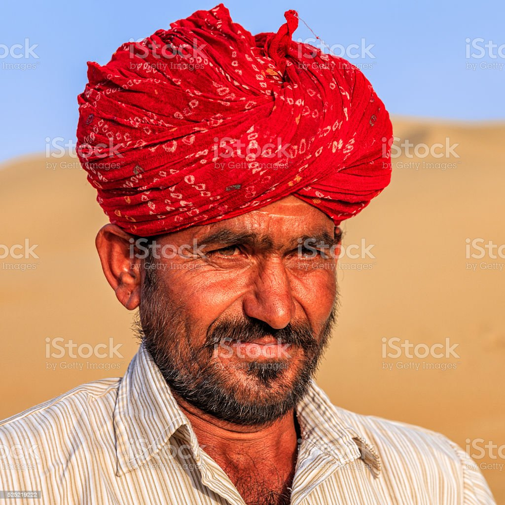 Portrait Indian man wearing turban, sand dunes, Rajasthan, India stock photo