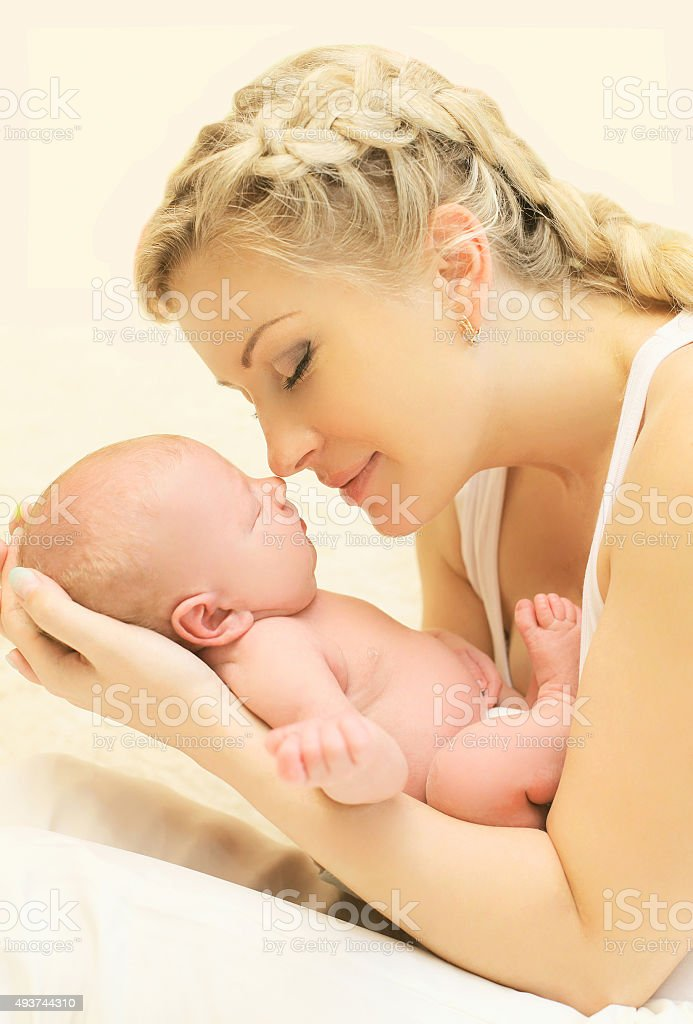 Portrait loving young mother holding on hands sleeping infant at stock photo