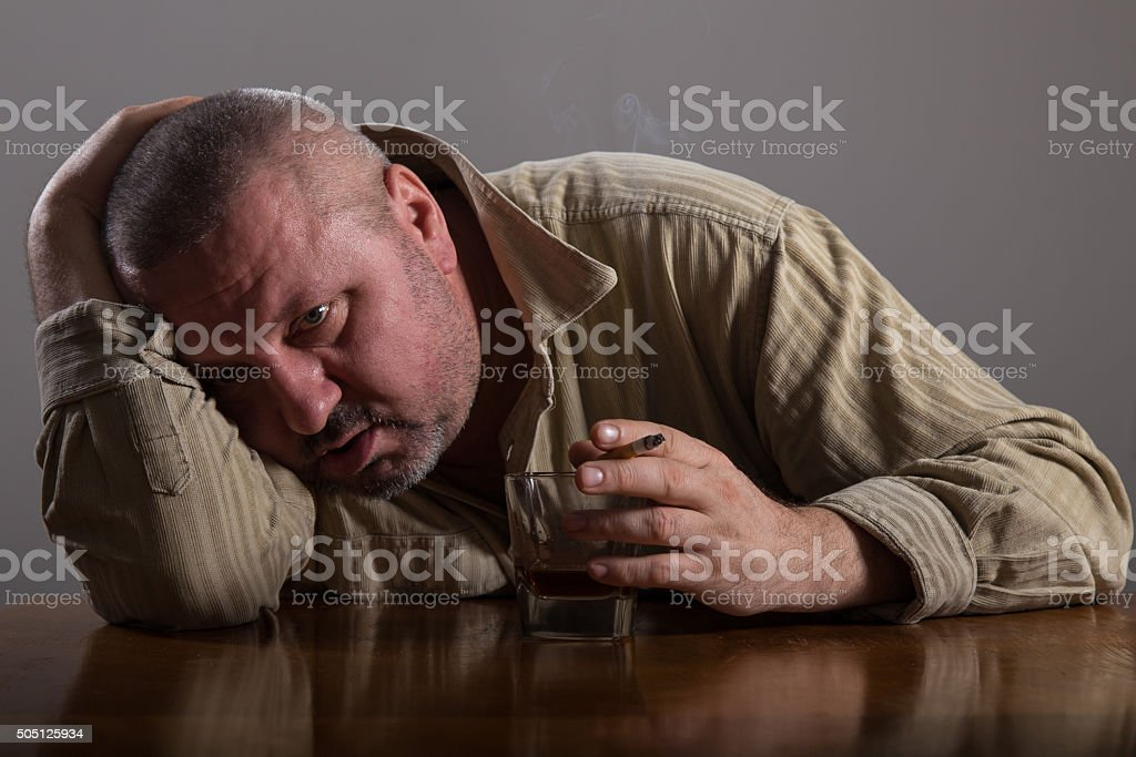 Portrait man drinking alcohol and smoking cigarette stock photo