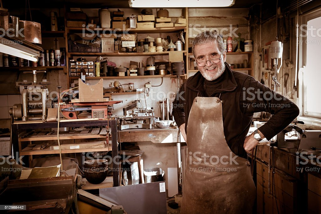 Portrait Master goldsmith working in his workshop stock photo