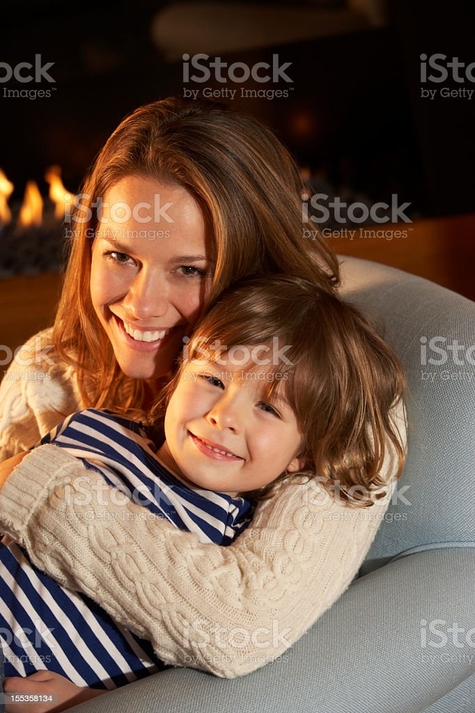 Portrait mother and son sitting in front of fire royalty-free stock photo