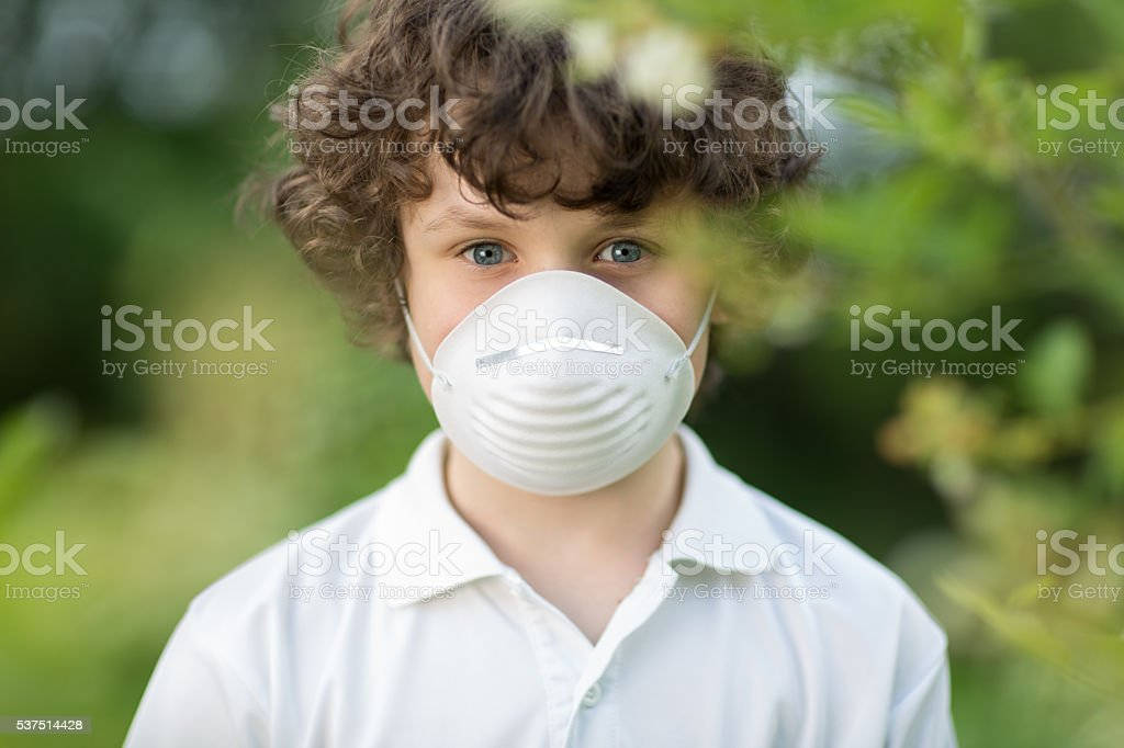 portrait of 9 years old boy with allergy wearing mask stock photo