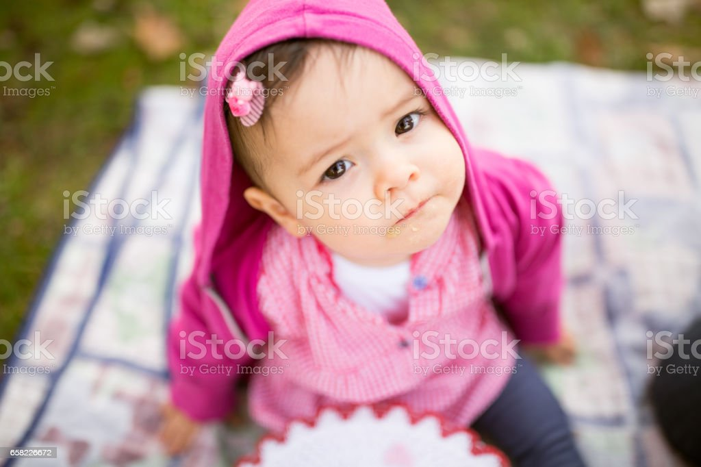 portrait of a beautiful baby girl sitting on a blanket in the park stock photo
