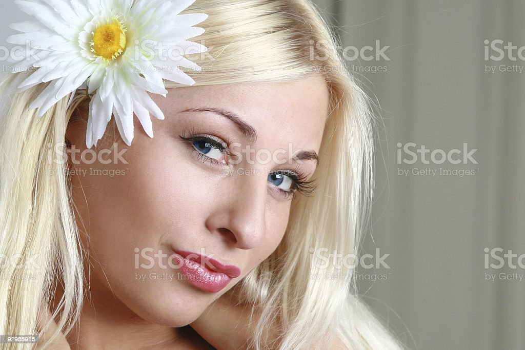 Portrait of a beautiful blond girl with camomile flower royalty-free stock photo