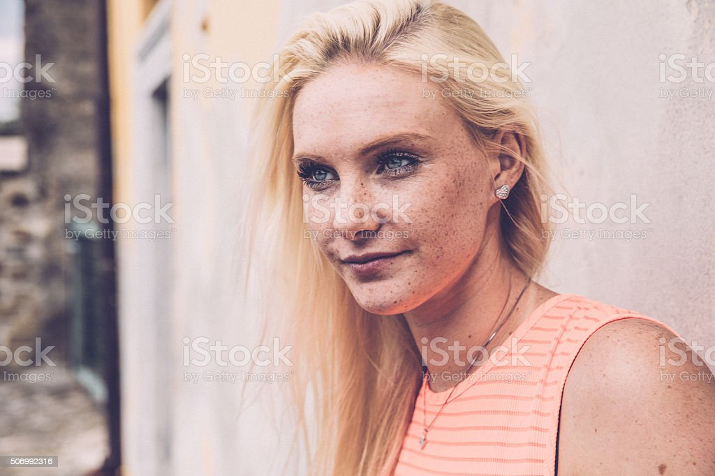 Portrait of a Beautiful Blonde Woman with Freckles Outdoors stock photo