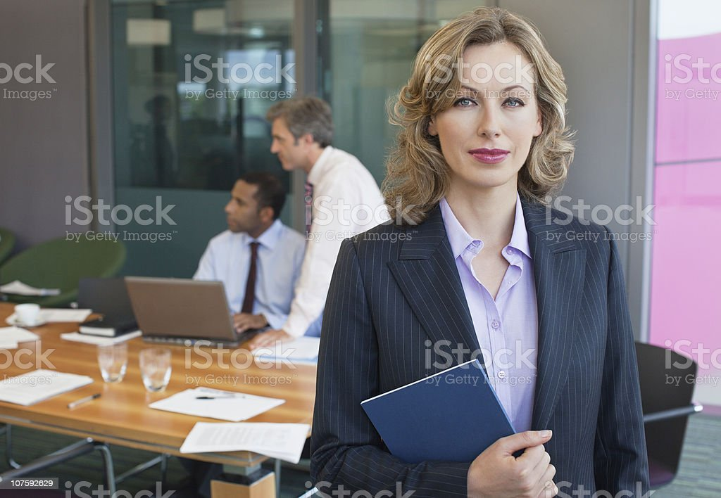 Portrait of a beautiful businesswoman with colleague in background at office royalty-free stock photo
