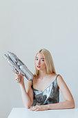 Portrait of a beautiful fashion blonde girl holding water gun