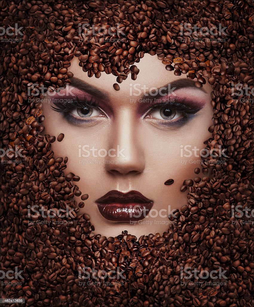 portrait of a beautiful girl in the coffee beans stock photo