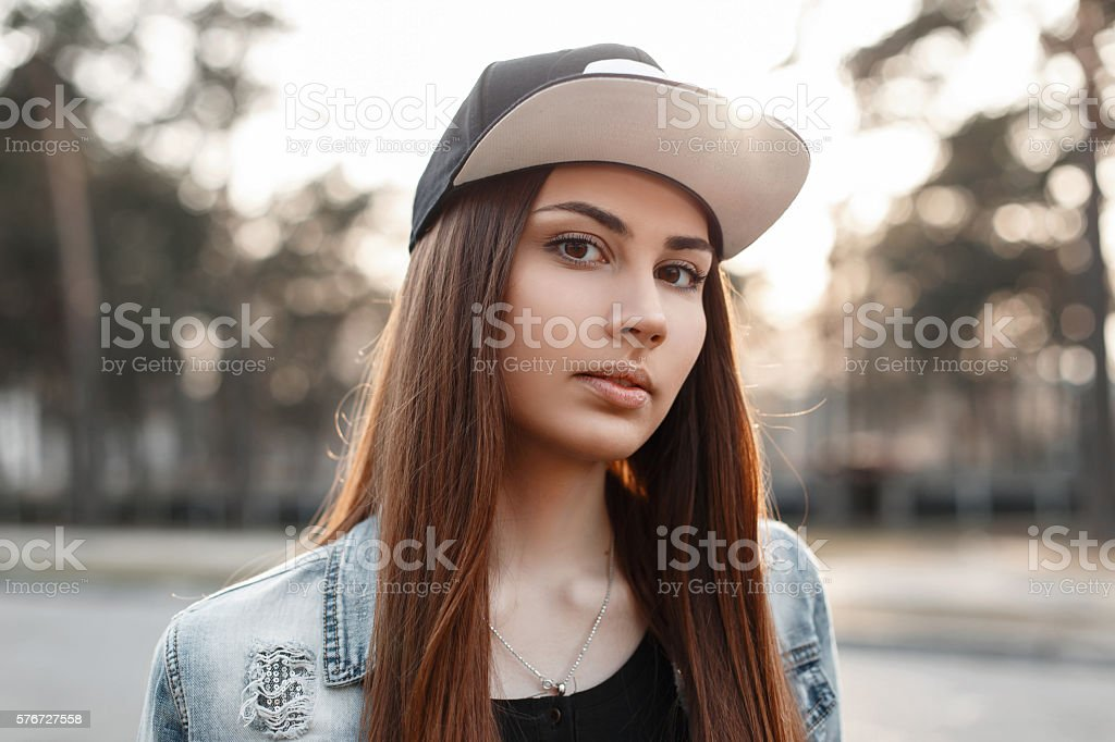Portrait of a beautiful hipster girl in a black cap stock photo