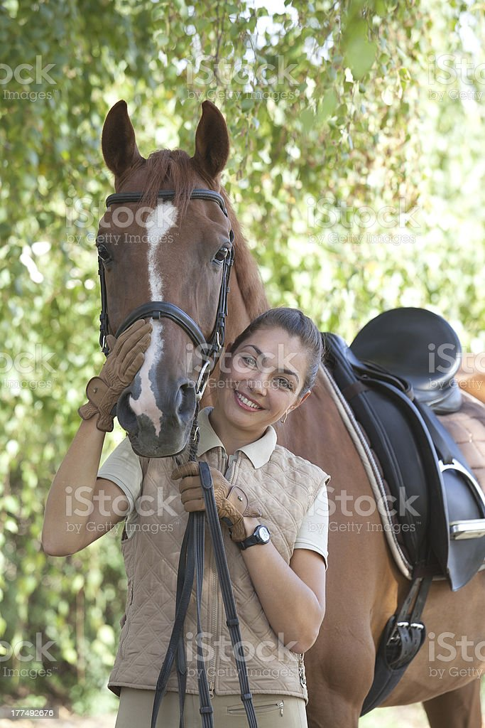 Portrait of a beautiful horsewoman standing with horse outdoors royalty-free stock photo