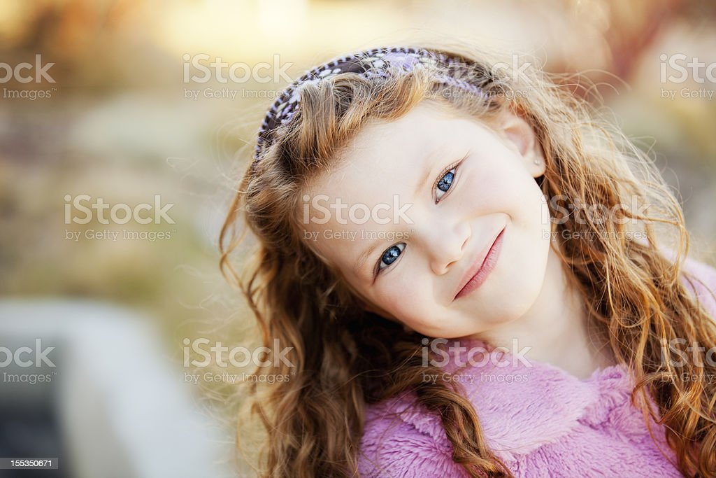 Portrait of a beautiful little girl outdoors stock photo