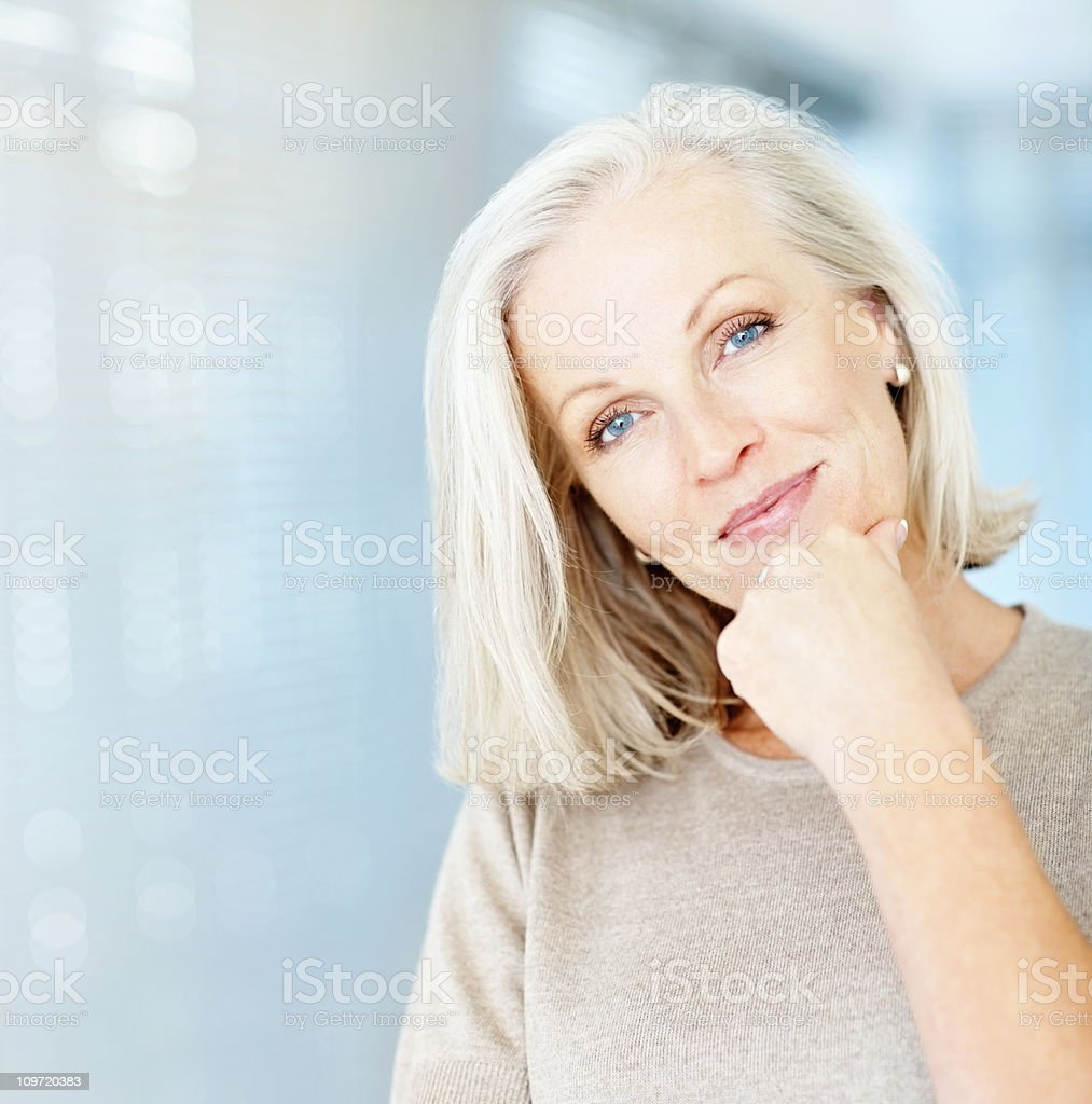 Portrait of a beautiful mature woman with hand on chin stock photo