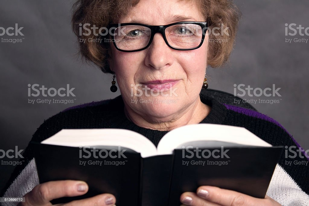 portrait of a beautiful older woman with glasses stock photo