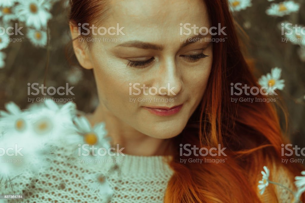 Portrait of a beautiful red-haired girl in a chamomile field stock photo