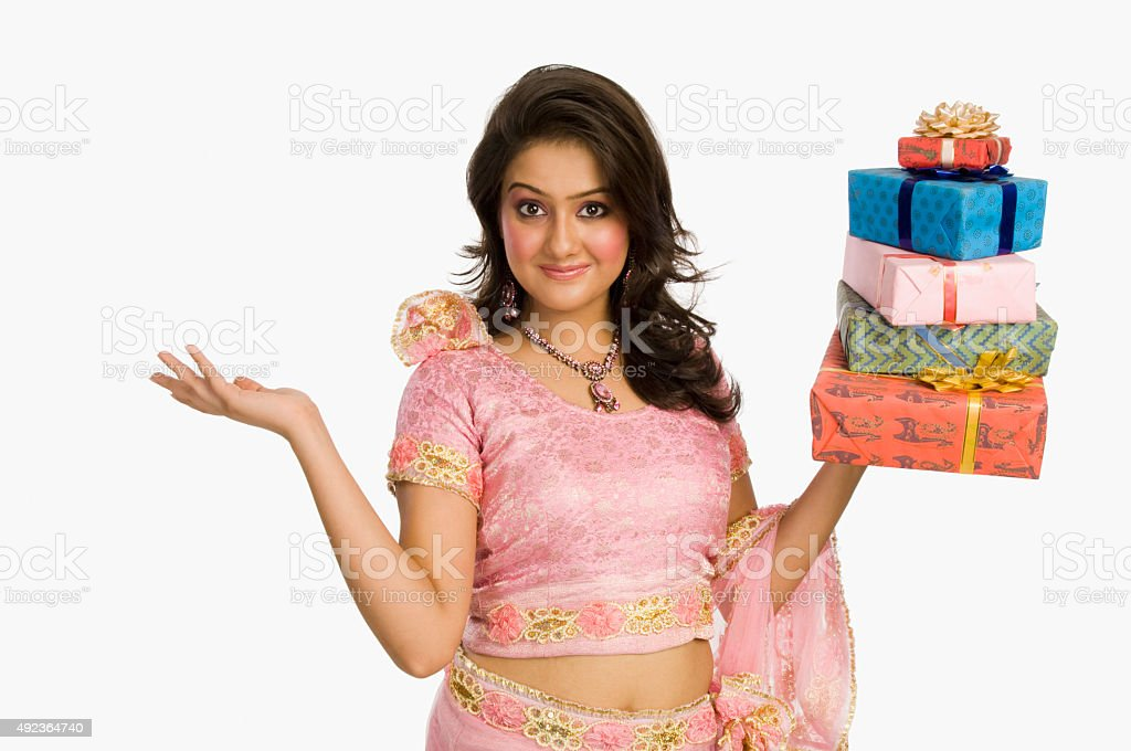 Portrait of a beautiful woman in traditional dress holding gifts stock photo