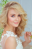 Portrait of a beautiful young blonde girl at white dress