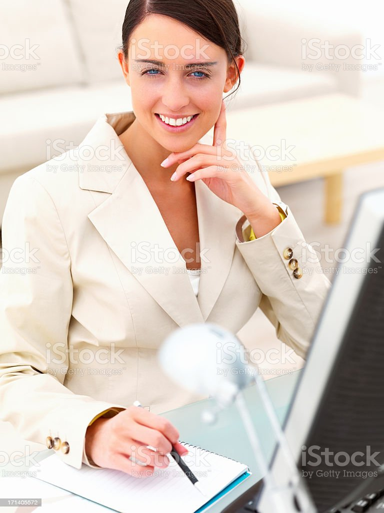 Portrait of a beautiful young businesswoman sitting by desk stock photo