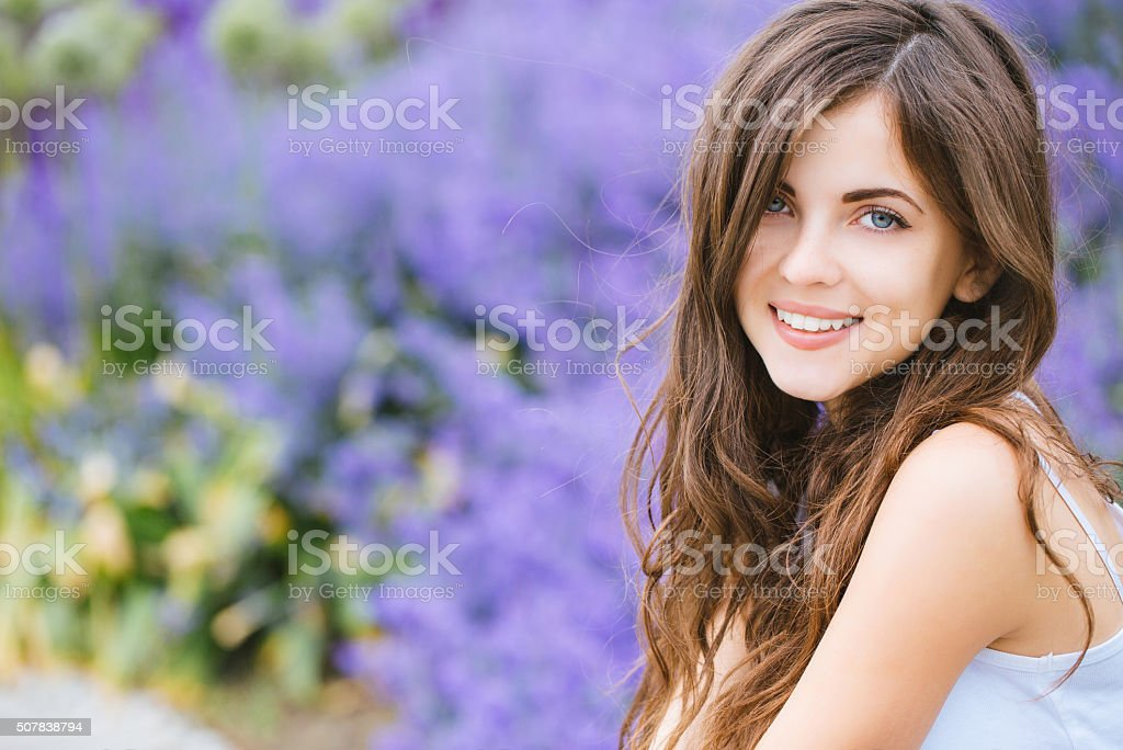 Portrait of a beautiful young student girl in the park stock photo