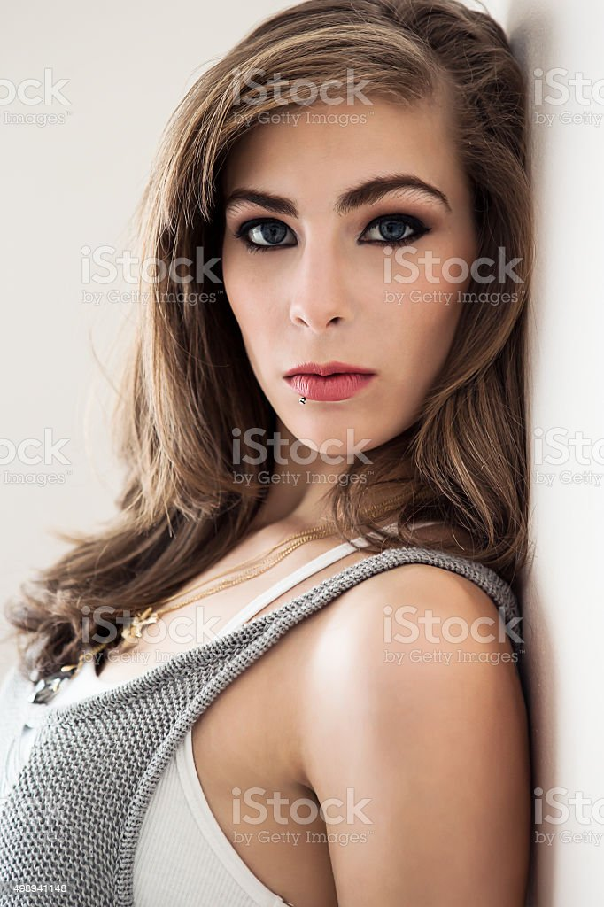 Portrait of a beautiful young woman against wall stock photo